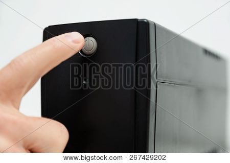 The Index Finger Is Pressing On The Start Button Of The Uninterrupted Power Supply.