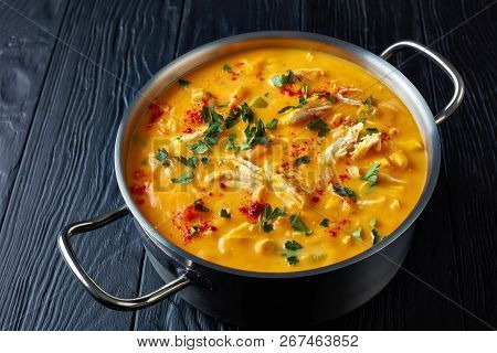 Overhead View Of Delicious Pumpkin Chicken Breast Savory Soup In Metal Casserole On Black Wooden Tab