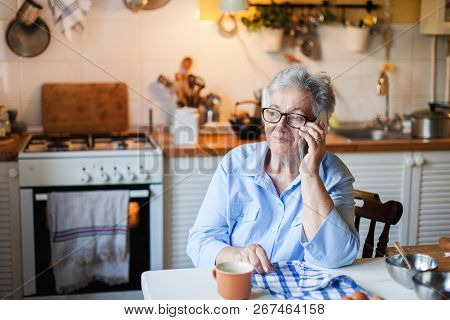 Senior Woman Is Talking On Mobile Phone At Cozy Home Kitchen. Grandmother Has Tea Or Coffee Break In