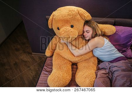Nice And Attractive Young Woman Sleeps. She Embraces Big Ber Toy With Pleasure. Woman Is Partly Cove
