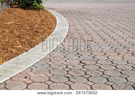 Curved Low Angle Brick Paver Driveway With Mulch