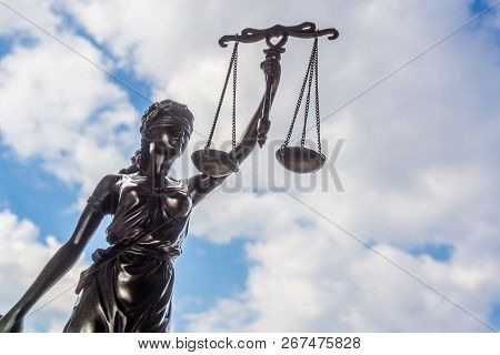 Statue Of Justice Against Blue Sky And Clouds. Legal Law Concept