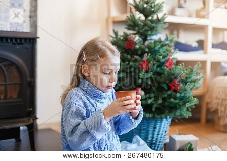 Child Girl Is Drinking Hot Beverages By Christmas Tree At Home. Kid Holds Mug With Steamy Tea Or Coc