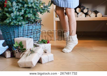 Little Child Girl Is Decorating Christmas Tree With Ornaments. Kid In Woolen Knitted Socks Stands On