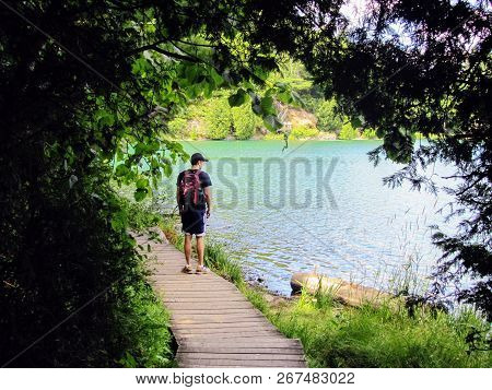 Man Standing On A Pathway By A Remote Lake Thinking And Contemplating Staring Out At The Water