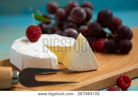 Cheese Camembert With Raspberries And Grapes On