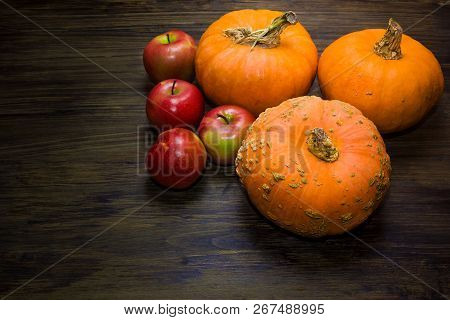 Pumpkins And Apples. Autumn Harvest Of Apples And Pumpkins On A Wooden Table. Red Apples.