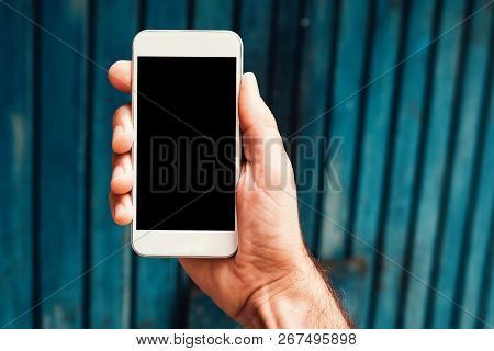 Hand With Smartphone Mock Up Screen In Urban Surrounding. Man Holding Mobile Phone Device With Blank