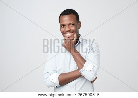 Portrait Of Happy Handsome African Man In White Shirt Crossing Hands And Looking At Camera