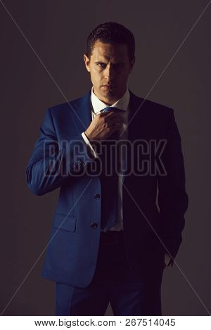 Successful Man, Confident Businessman Or Handsome Boss Adjusting Tie In Stylish Blue Formal Suit And