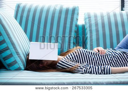Beautiful Young Asian Woman Sleeping On Sofa With Book Covering Her Face Because Reading Book With P
