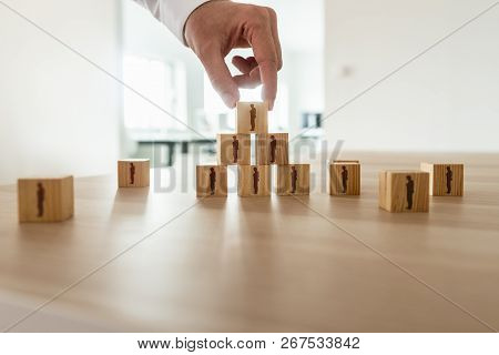 Businessman Arranging Wooden Cubes With People Silhouette In A Pyramid Shape With Others Scattered O