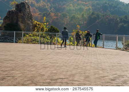 Gumsan, South Korea; November 4, 2018: Four Unidentified Asians Standing At Fence Overlooking Lake W