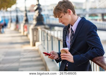 Male young adult teenager wearing suit and tie using smart cell phone for socail media and drinking takeout coffee poster