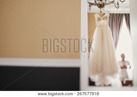 Bride Looking At Stylish Wedding Dress. Modern Wedding Gown Hanging On Chandelier In Room. Space For