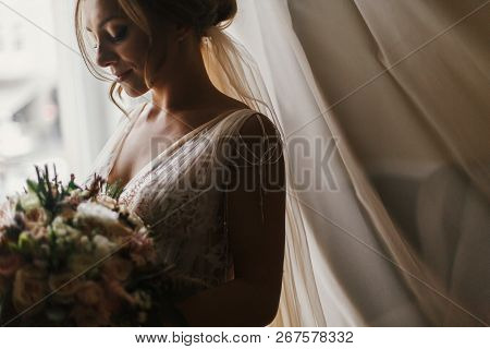 Gorgeous Beautiful Bride With Bouquet Posing At Window In Soft Light. Happy  Bride In Stylish Gown A