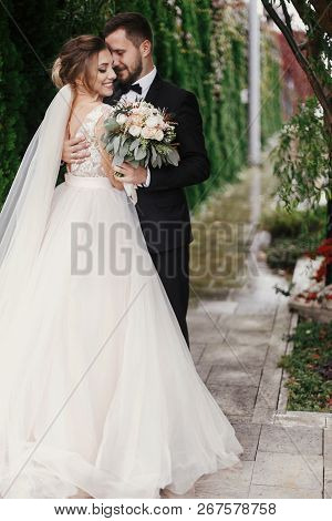 Gorgeous Bride And Stylish Groom Gently Hugging On Background Of Green Trees. Sensual Wedding Couple