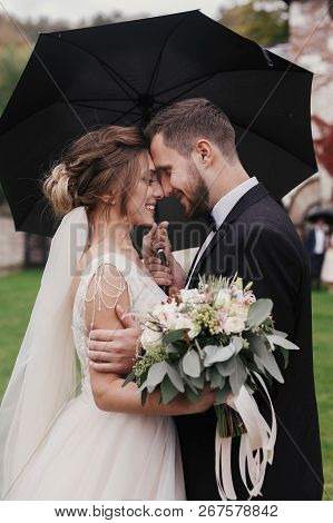 Gorgeous Bride And Stylish Groom Gently Hugging Under Umbrella In Rainy Outdoors. Sensual Wedding Co