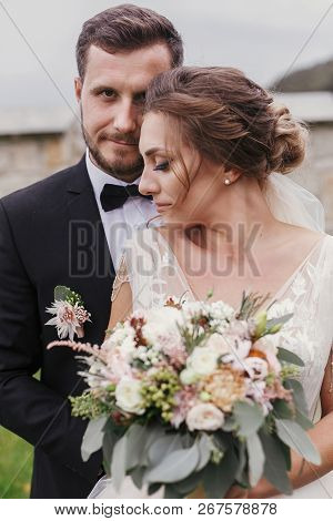 Gorgeous Bride With Modern Bouquet And Stylish Groom Gently Hugging And Smiling Outdoors. Sensual We