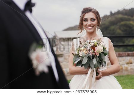 Gorgeous Bride With Modern Bouquet Looking At Stylish Groom And Smiling Outdoors. Sensual Wedding Co