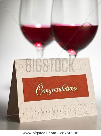 congratulation card in front of the red wine glass