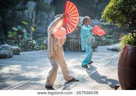 Chengdu, Sichuan Province, China - Oct 31, 2018 : Man And Woman Practising Tai Chi With Red Fans In