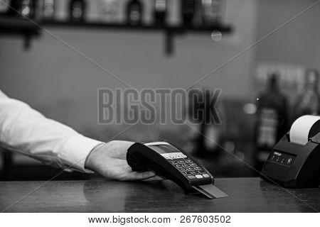 Cashiers Hand Holds Credit Card Reader On Defocused Background