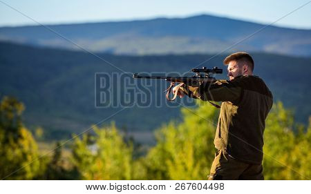Hunter khaki clothes ready to hunt hold gun mountains background. Hunter with rifle looking for animal. Hunting shooting trophy. Man rifle for hunt. Mental preparation for hunting individual process poster