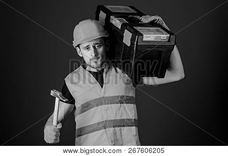 Man In Helmet, Hard Hat Carries Toolbox And Holds Hammer, Blue Background. Worker, Repairer, Repairm