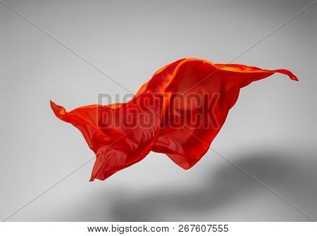 abstract piece of orange fabric flying, high-speed studio shot