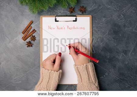 Woman Hands Ready To Write New Years Resolutions On Blank List.flat Lay. Top View. New Year Concept.
