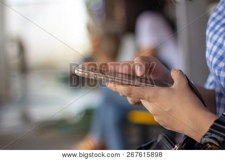 Close Up Woman Hand Using Smart Phone Outdoors Side View, Another Girl Using Mobile Phone In Backgro