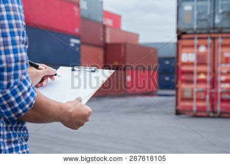 Man Taking Note Checking Cargo Shipping At Container Yard Area. Worker Man Signing Papers About Impo
