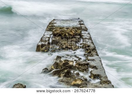 Old Pier In The Sea Drowned By Waves
