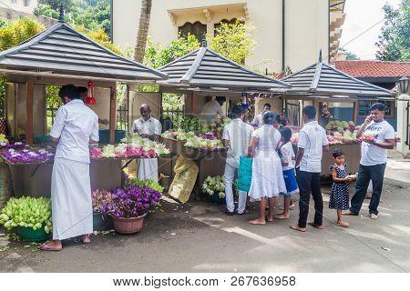 Kandy, Sri Lanka - July 19, 2016: White Clothed Buddhist Devotees Buy Lotus Flowers During Poya Full