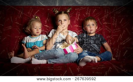 Childrens Movies: Three Children Watch Movies At Home On A Big Red Sofa In The Dark And Eat Popcorn.