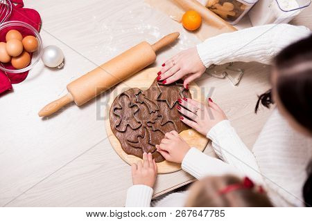 Top View Of Little Girl And Her Mother Cooking Christmas Cookies Or Gingerbreads In Kitchen