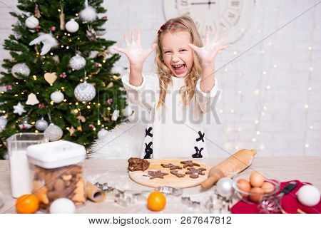 Funny Little Girl Cooking Christmas Cookies In Kitchen With Christmas Tree