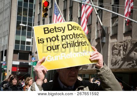 March For Our Lives: Close up of a man holding a sign that says Betsy Devos Is Not Protecting Our Children during the march to end gun violence on 6th Ave, NEW YORK MAR 24 2018.
