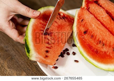 Sliced Watermelon In A Plate On A Wooden Table. A Knife Removes Seeds From A Lobule.