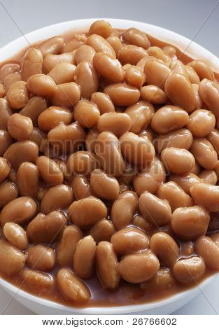 Bowl of baked beans isolated on white background.