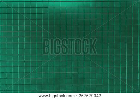 Closeup Of A Green Colored Tiled Wall. View To A Green Shiny Metallic Wall. Geometric Shapes And Bac