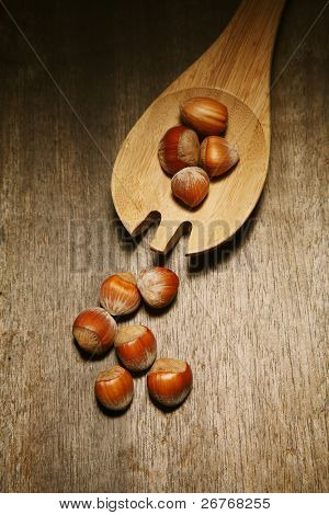 Hazelnuts on a table along with a cooking utensil.