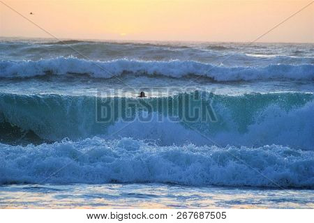 Large Waves Crashing Over A California Beach While A Surfer Swims Out To Catch The Surf.