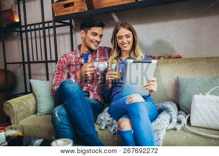Portrait Of Happy Young Couple Using A Digital Tablet Together At A Coffee Shop. Young Man And Woman