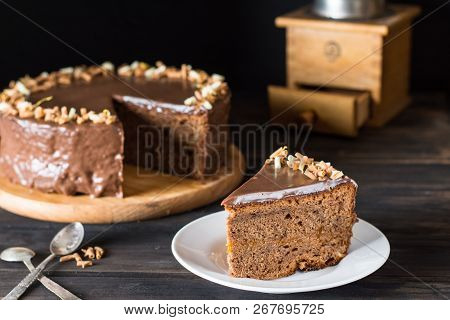 Piece Of Chocolate Cake On A White Plate On Wooden. Traditional Austrian Cake. Sacher Cake. Apricot