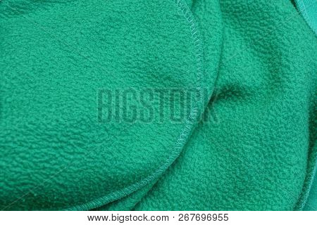 Green Background Of Crumpled Fabric On Clothes