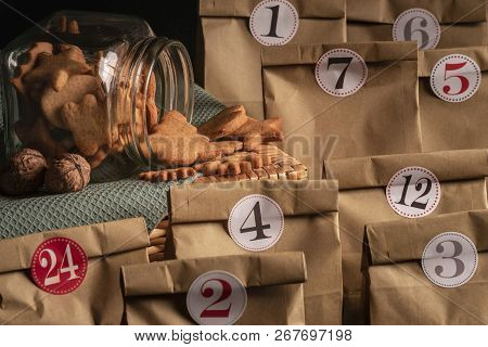 Overturned Glass Jar Full With Gingerbread Christmas Cookies Surrounded By Numbered Paper Bags, A Se