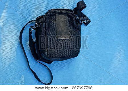 Black Cloth Bag Lying On A Blue Paper Sheet