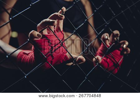 Female Fist In Bandages For Boxing Grabs Ring Grille. Concept Of Loneliness, Struggle, Society Indif